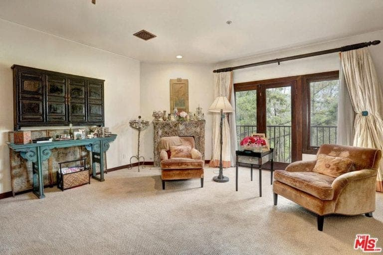 Large Mediterranean living featuring carpet flooring, a nice set of seats and a stylish fireplace on the corner.