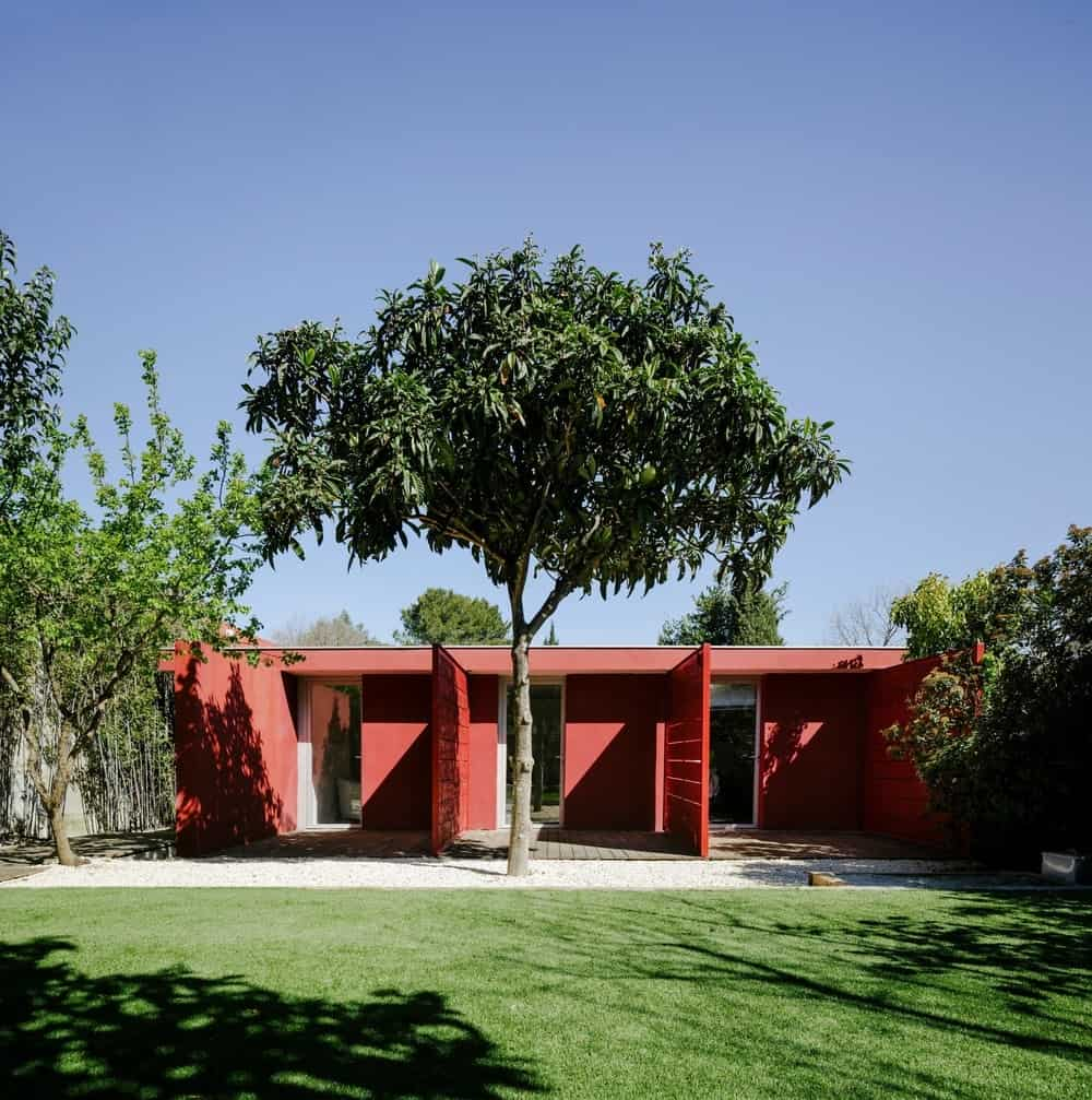 Another outdoor view of the red GOM House with huge backyard. Photo credit: Julien Kerdraon