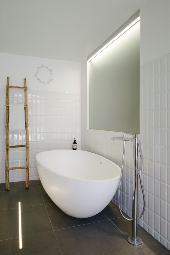 This bathroom boasts stylish tiles flooring and a freestanding tub and shower combo.