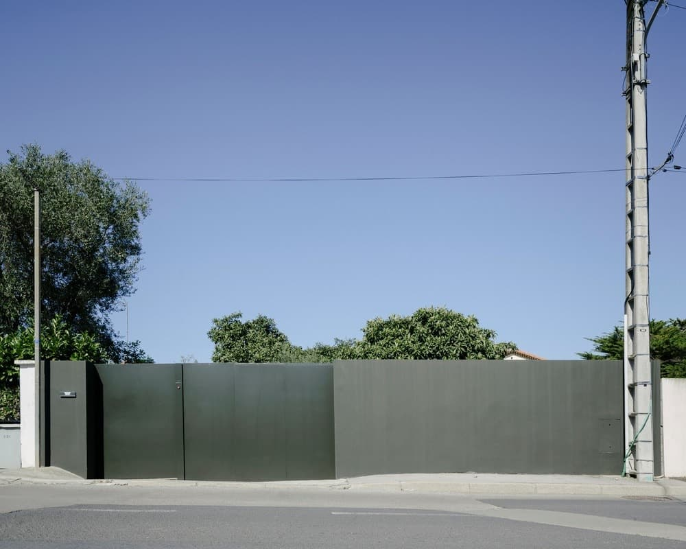 A view of the property's large gray gate from afar. Photo credit: Julien Kerdraon