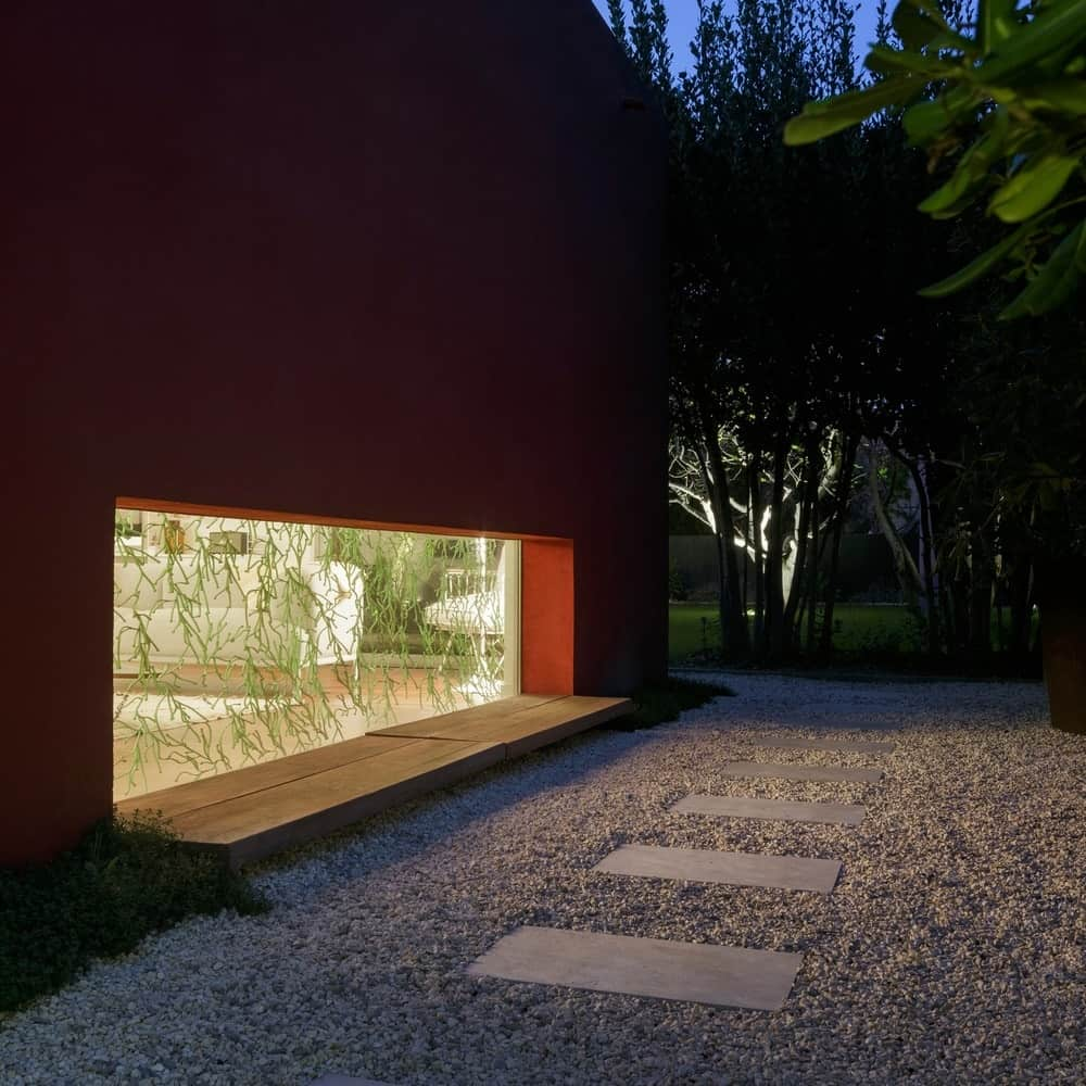 Outside view of the home in red concrete and glass wall and a gravel walkway. Photo credit: Julien Kerdraon