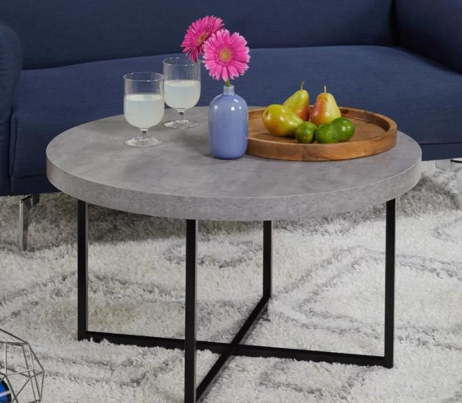 Round coffee table with a gray laminate top and a black metal base.