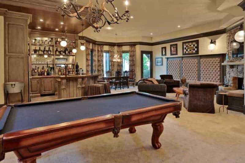 This home features a rustic bar area and a billiards pool set on the carpet flooring. There's a living space with a fireplace and a dining table set lighted by a gorgeous chandelier.