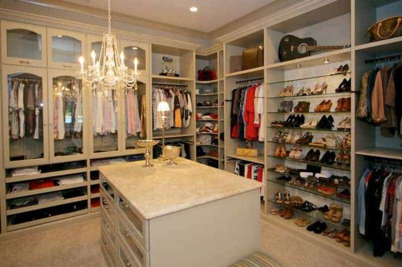 Elegant bedroom closet featuring white walls, cabinetry and a center island with marble countertop lighted by a classy chandelier.