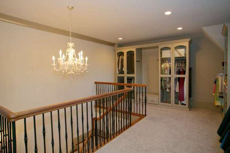 A reach-in closet near the staircase features a chandelier and recessed ceiling lights.
