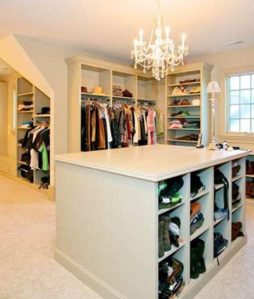 Walk-in closet boasts a carpet flooring, an island, shoe storage and multiple shelving.