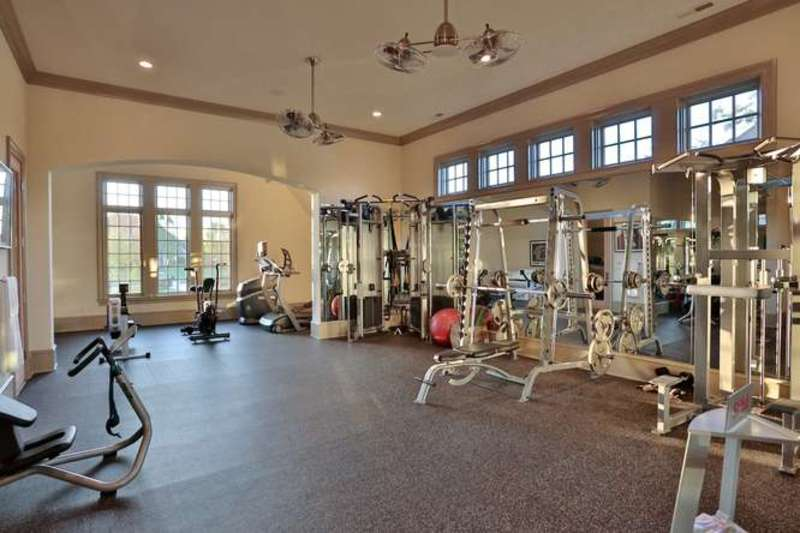 The gym boasts a near complete set of equipment on a carpet flooring.