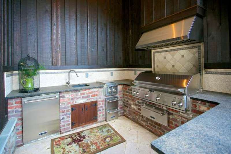 Outdoor kitchen boasts a nice set of stainless steel appliance and granite countertops.