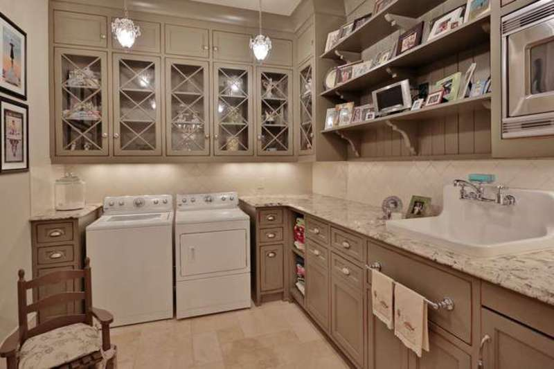 The laundry room features marble counters with multiple built-in closet along with a sink.