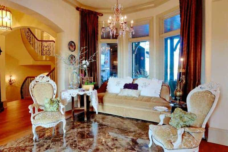 This living room is oozing with elegance with its sparkling bright flooring that mirrors the lights coming from the stunning chandelier. The red window curtains make the room look so romantic.