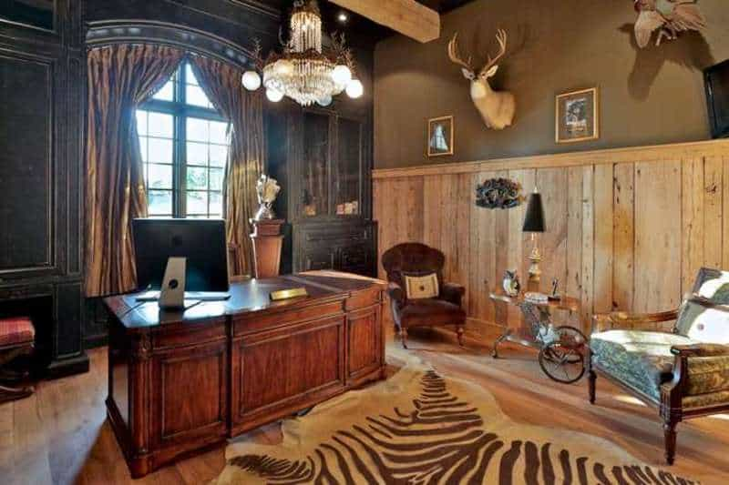A home office also exists in the house featuring a stylish rug on a laminated flooring lighted by a grand chandelier.