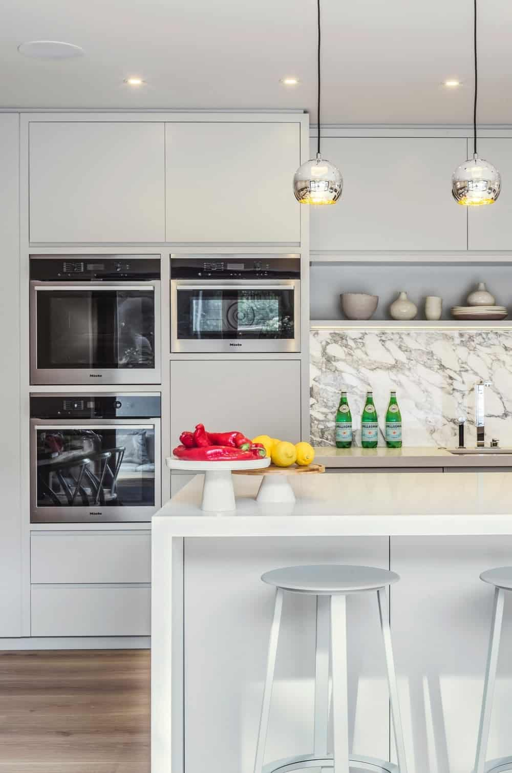 Contemporary kitchen with large center island and breakfast bar along with white cabinets and stainless steel appliance. Photo credit: Photography / Styling : Rick Mccullagh / LLI Design