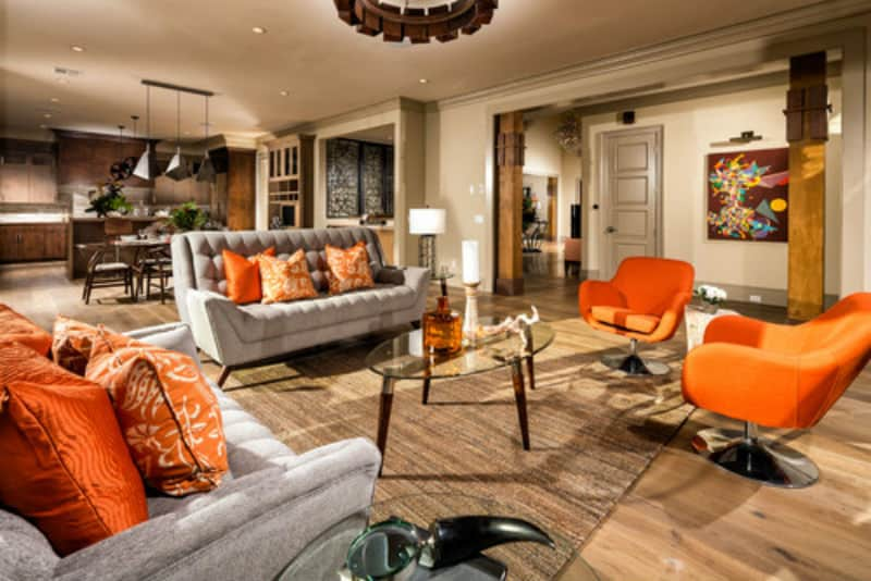 Modern living room with touches of brown, grey, black, and orange.