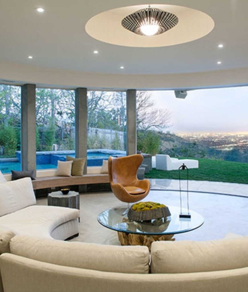 The living room features a rounded shape lighted by pendant and recessed lights. The area also offers an astonishing view of the outdoor landscape.