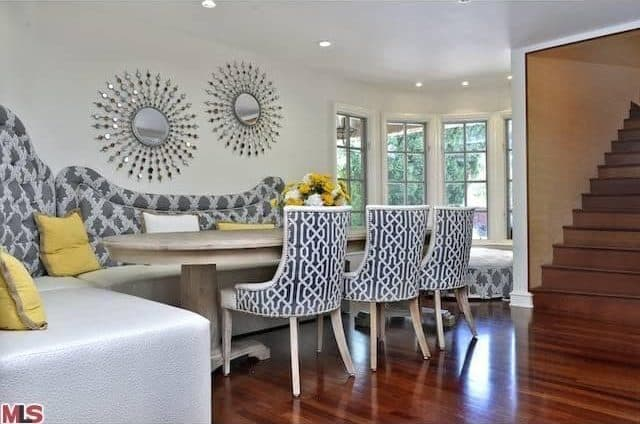 Oval dining table offers contemporary set of chairs and couch seating. Recessed lights brighten the area.