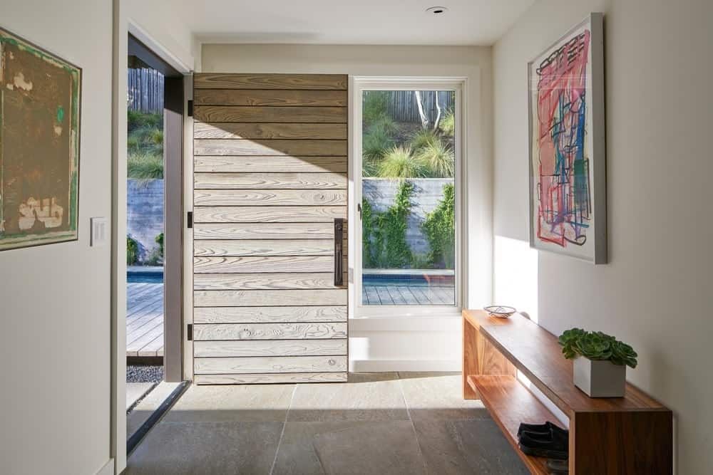 Kentfield Residence home entry with white walls and a nice wall decor along with a wooden shoe rack. Photo credit: Bruce Damonte