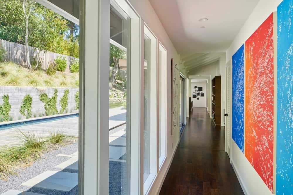 Hallway with white and glass walls combo along with hardwood flooring and recessed lights. Photo credit: Bruce Damonte