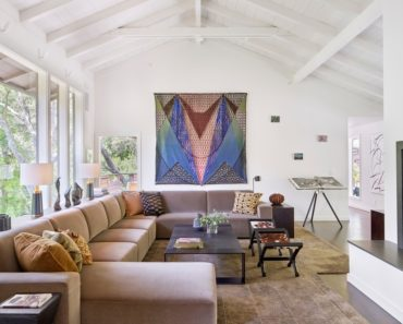 Living room with white walls and vaulted ceiling together with wide sofa set on a nice rug. Photo credit: Bruce Damonte