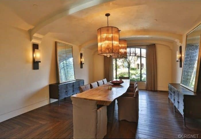 This dining room features a tree stump dining table and skirted chairs in between dark wood buffet tables topped with large mirrors and lighted by wall sconces.