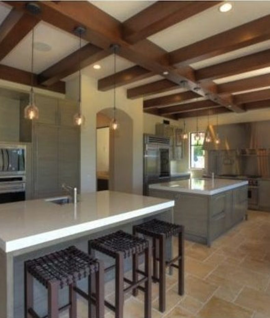 The kitchen has two islands with beams ceiling lighted by recessed ceiling lights.