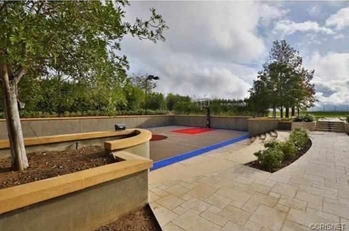 The property also has a basketball court surrounded by healthy trees.