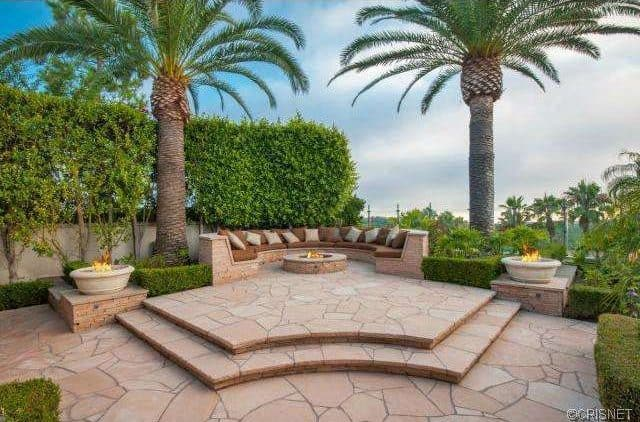 The patio with a fire pit is perfectly placed in-between two beautiful tropical trees.