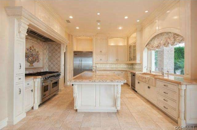 Large Mediterranean kitchen with classy cabinetry and counters equipped with marble countertops. The classy tiles flooring looks glamorous.