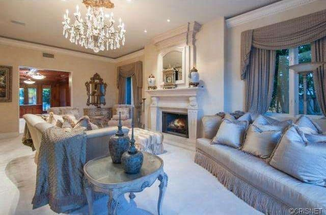 Luxury living room boasts a fancy chandelier and gray sofas filled with fluffy pillows. It has carpet flooring and glazed windows covered with gray draperies and valences.