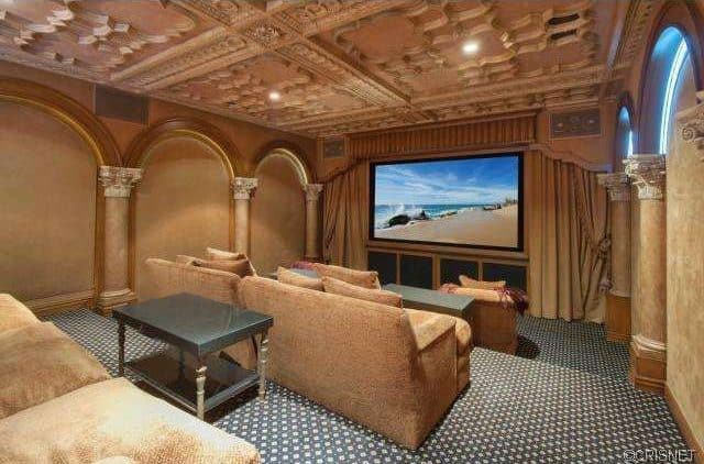 The home theater offers elegant seating and wide screen TV. The carpet perfectly blends with the beige walls.