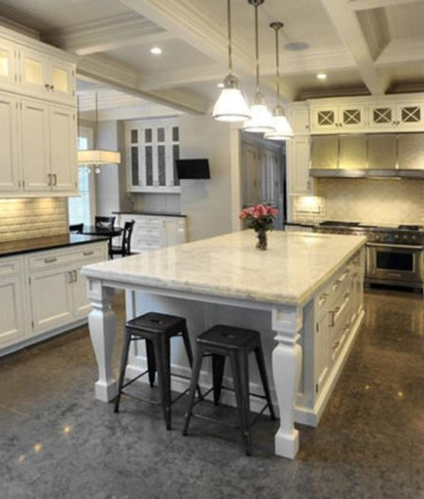 Custom luxury white kitchen with pendant lights over island that has breakfast bar on end