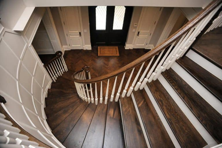 Curved elegant hardwood staircase leading to foyer