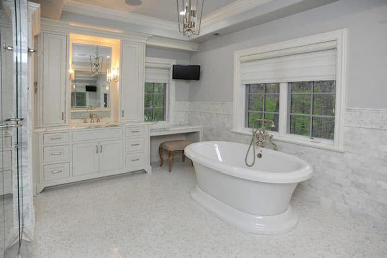 Sumptuous white primary bathroom with freestanding tub