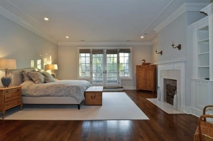 This master bedroom offers a large bed and a fireplace, along with hardwood flooring topped by a white rug.