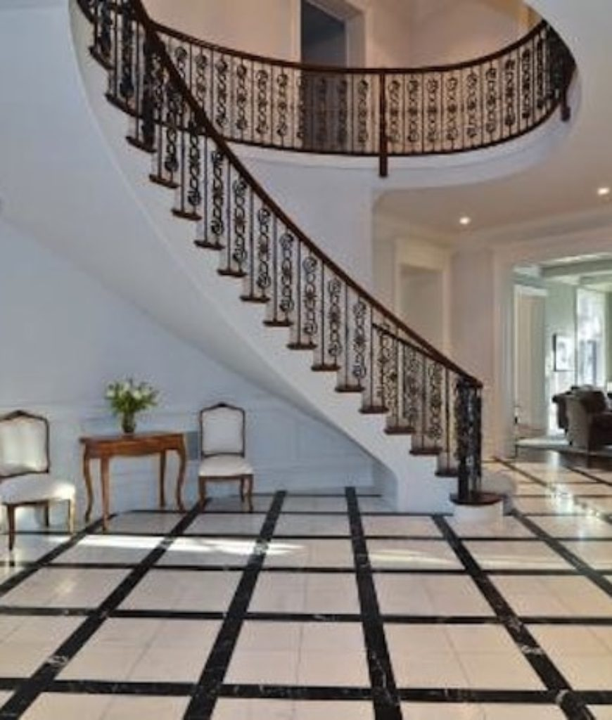 Grand foyer greets family and friends upon entering the house. Beautiful tiles flooring matches well with white built of the space.