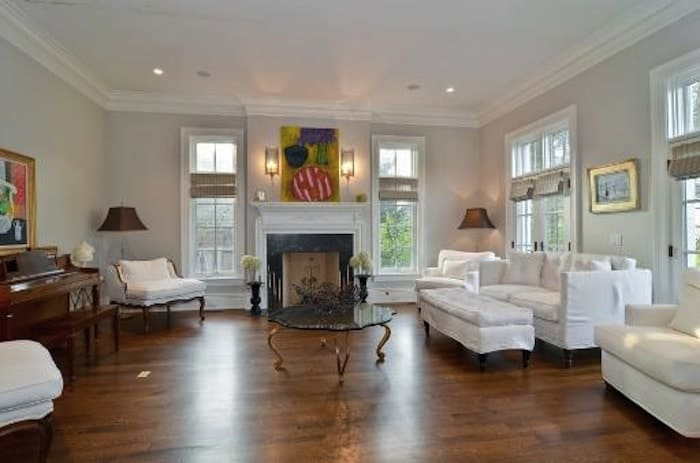 Another living space provides white seating lounge near the fireplace. Laminated flooring perfectly fits the white walls and ceiling of the room.