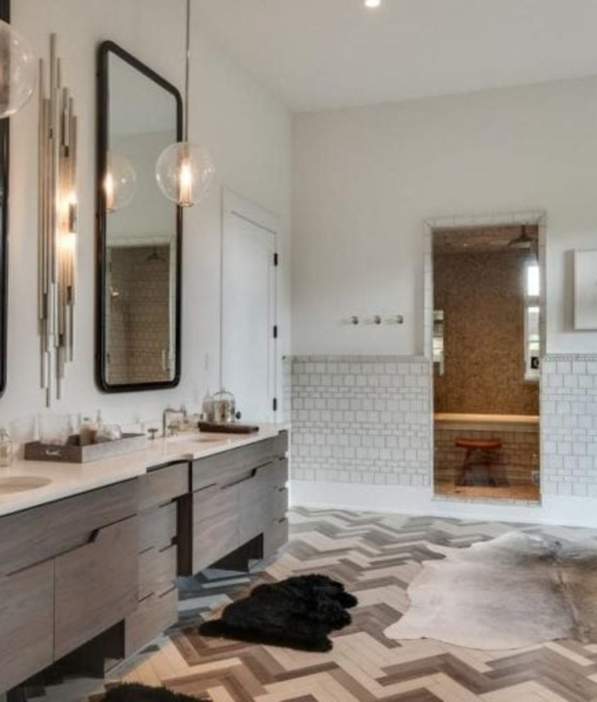 The bathroom features stylish flooring and sink along with its pendant lights.