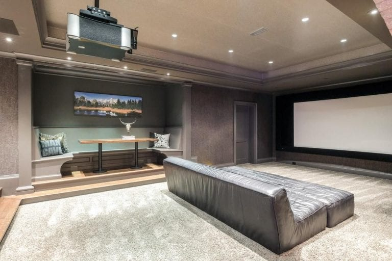 The home theater is spacious with a theater sofa seat and a dining nook on the side.