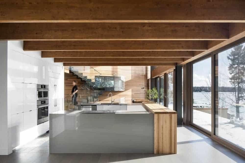White U-shape kitchen with hardwood flooring and glass walls.