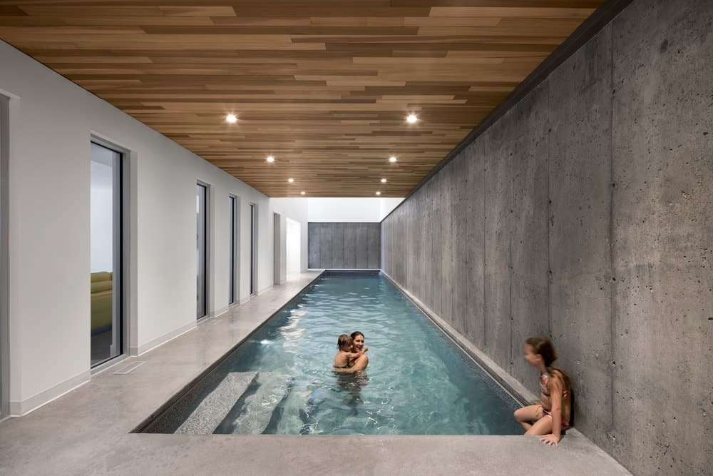 Long Rectangular Pool With Hardwood Ceiling And Recessed Ceiling Lights.