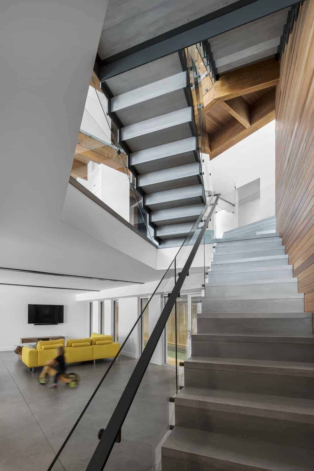 Half-turn staircase with hardwood walls and steel with glass rail.