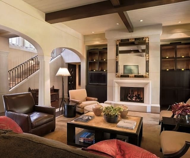 This Mediterranean living room features white walls and dark wooden side shelves and cabinets. The fireplace looks perfect together with this room.