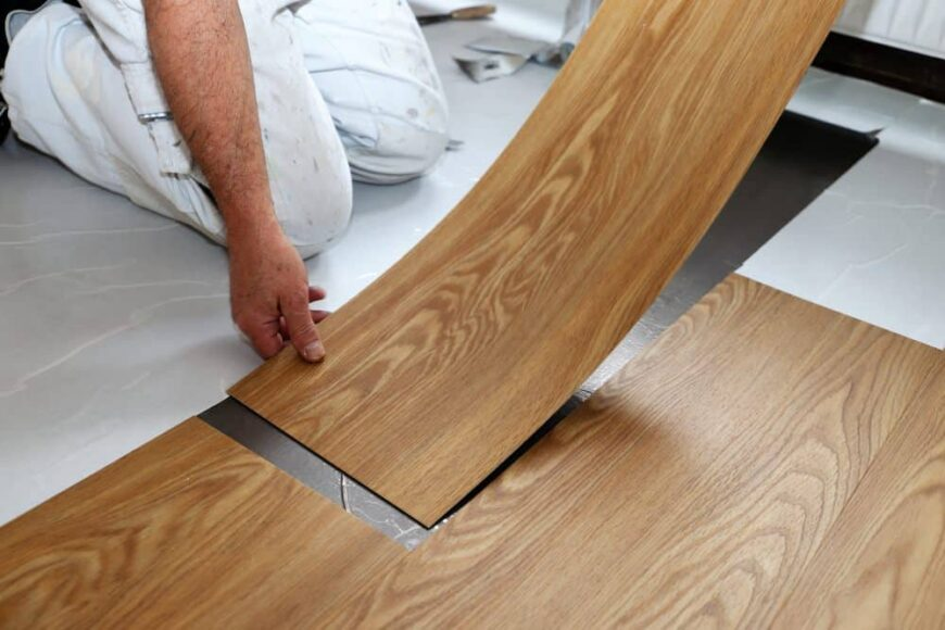 Man laying down luxury vinyl tile flooring