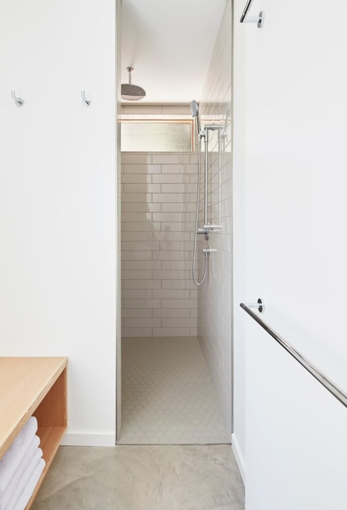 This bathroom features white walls and classy marble flooring. The bathroom also offers an open shower room.