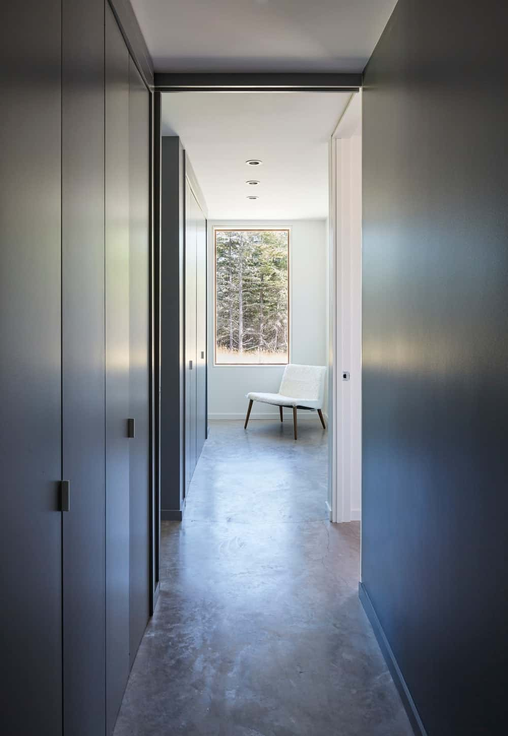 Hallway leading to different parts of the house featuring smooth flooring and recessed ceiling lights. Photo credit: Janet Kimber