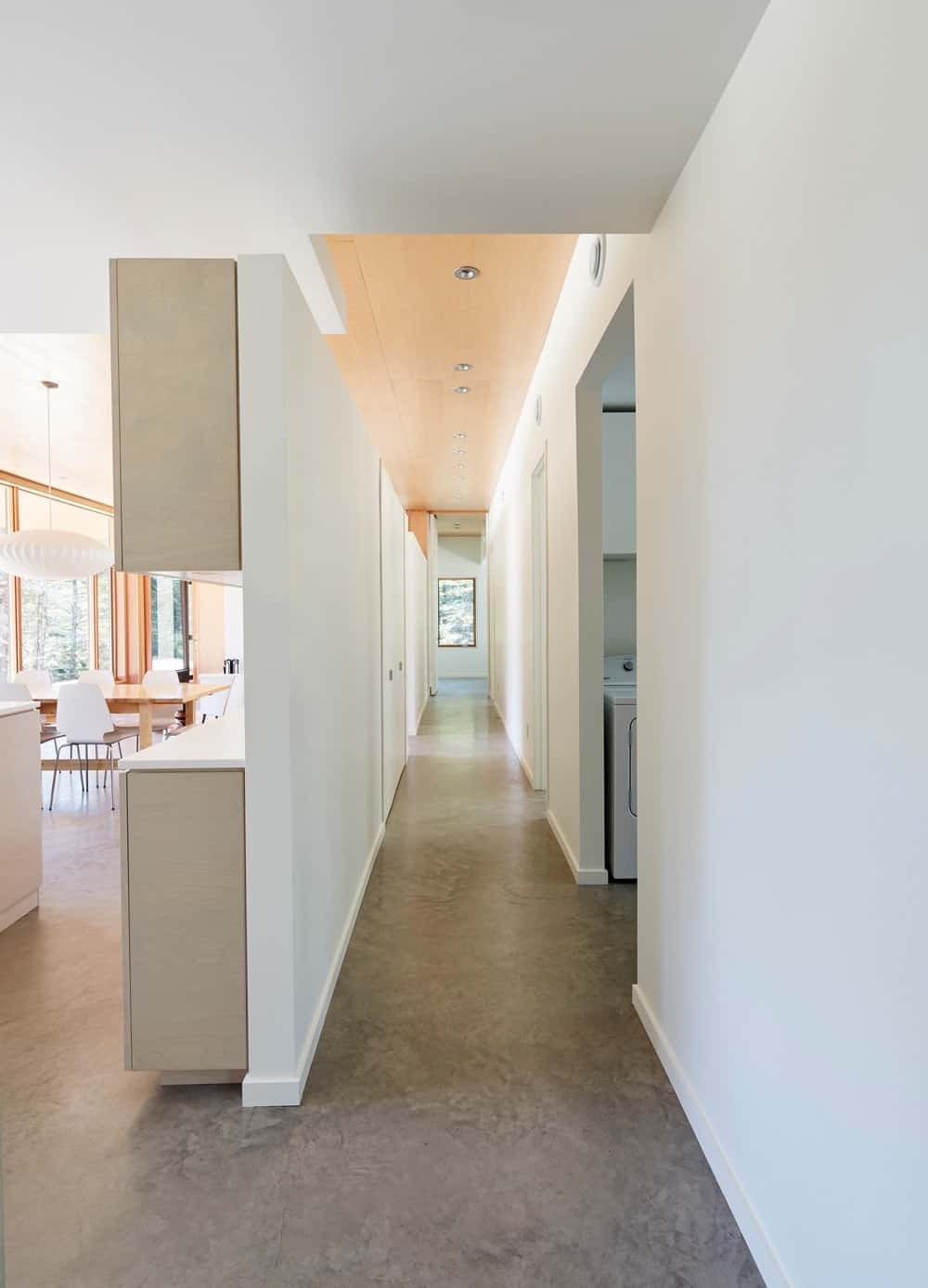 Hallway leading to kitchen white white walls and smooth flooring along with recessed ceiling lights. Photo credit: Janet Kimber