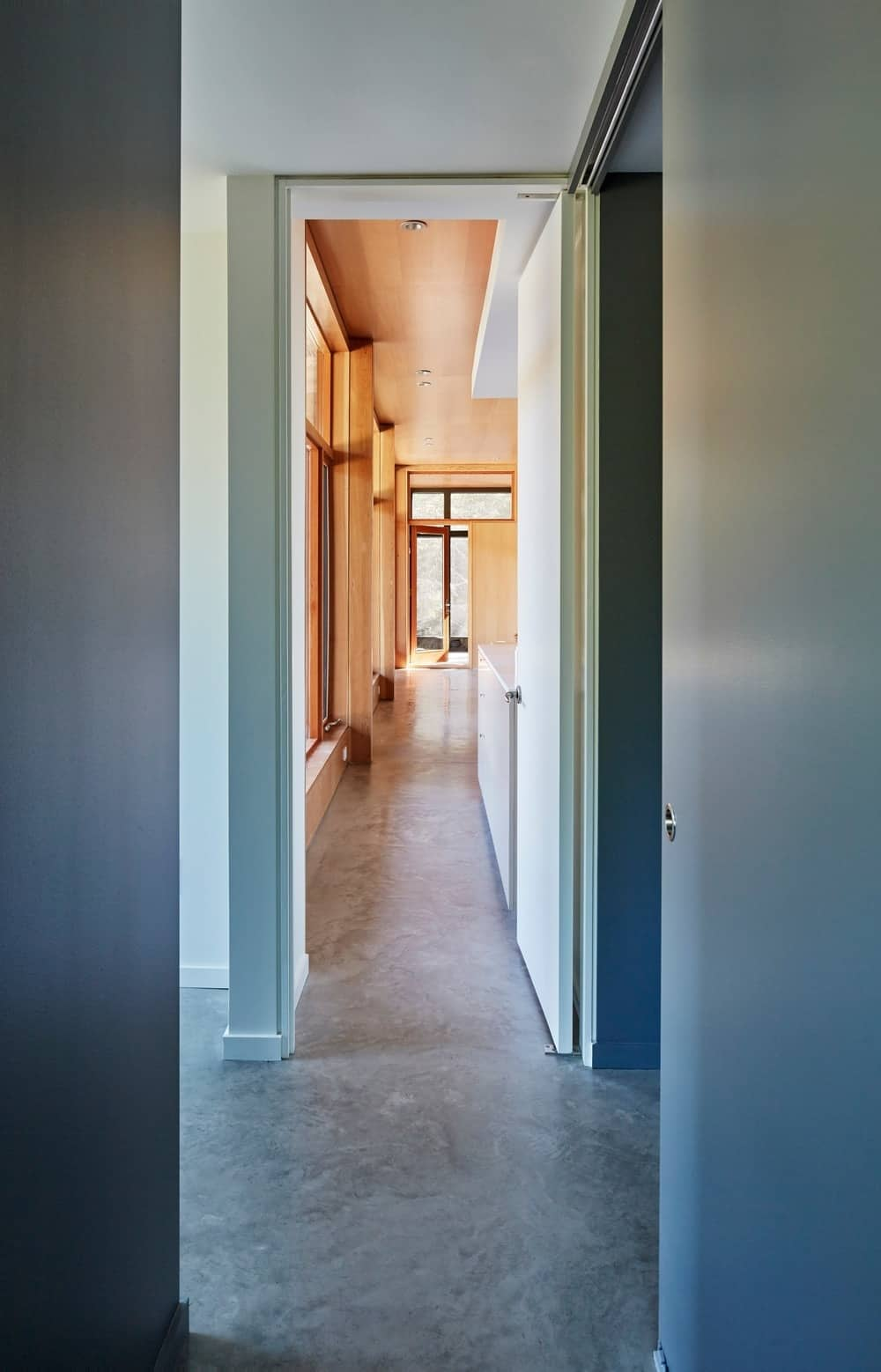 Hallway leading to different parts of the house featuring smooth flooring. Photo credit: Janet Kimber
