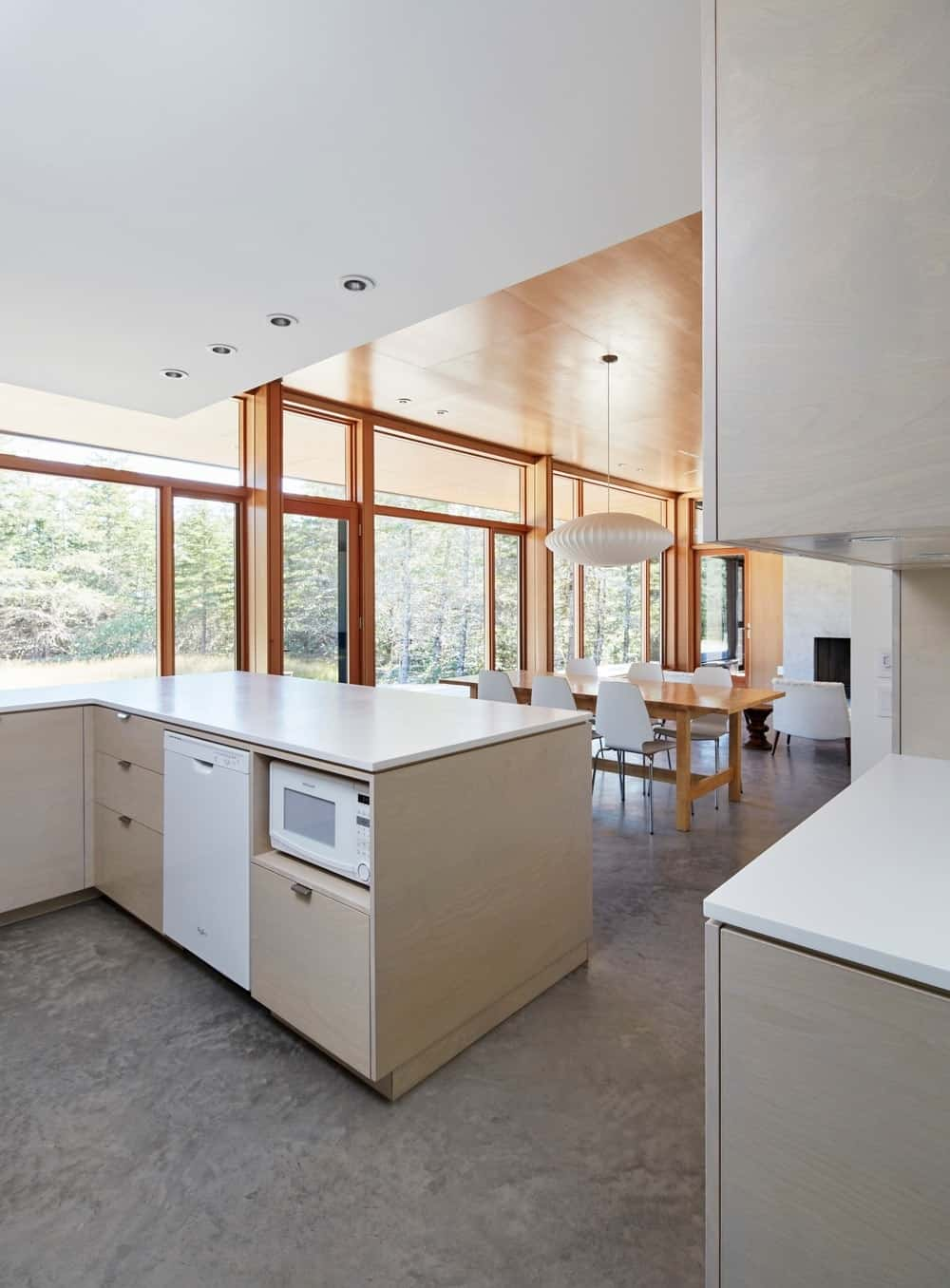 A dine-in kitchen offers white appliances fitted along the light wood cabinetry. It has concrete flooring and panoramic windows overlooking an enchanting forest view.