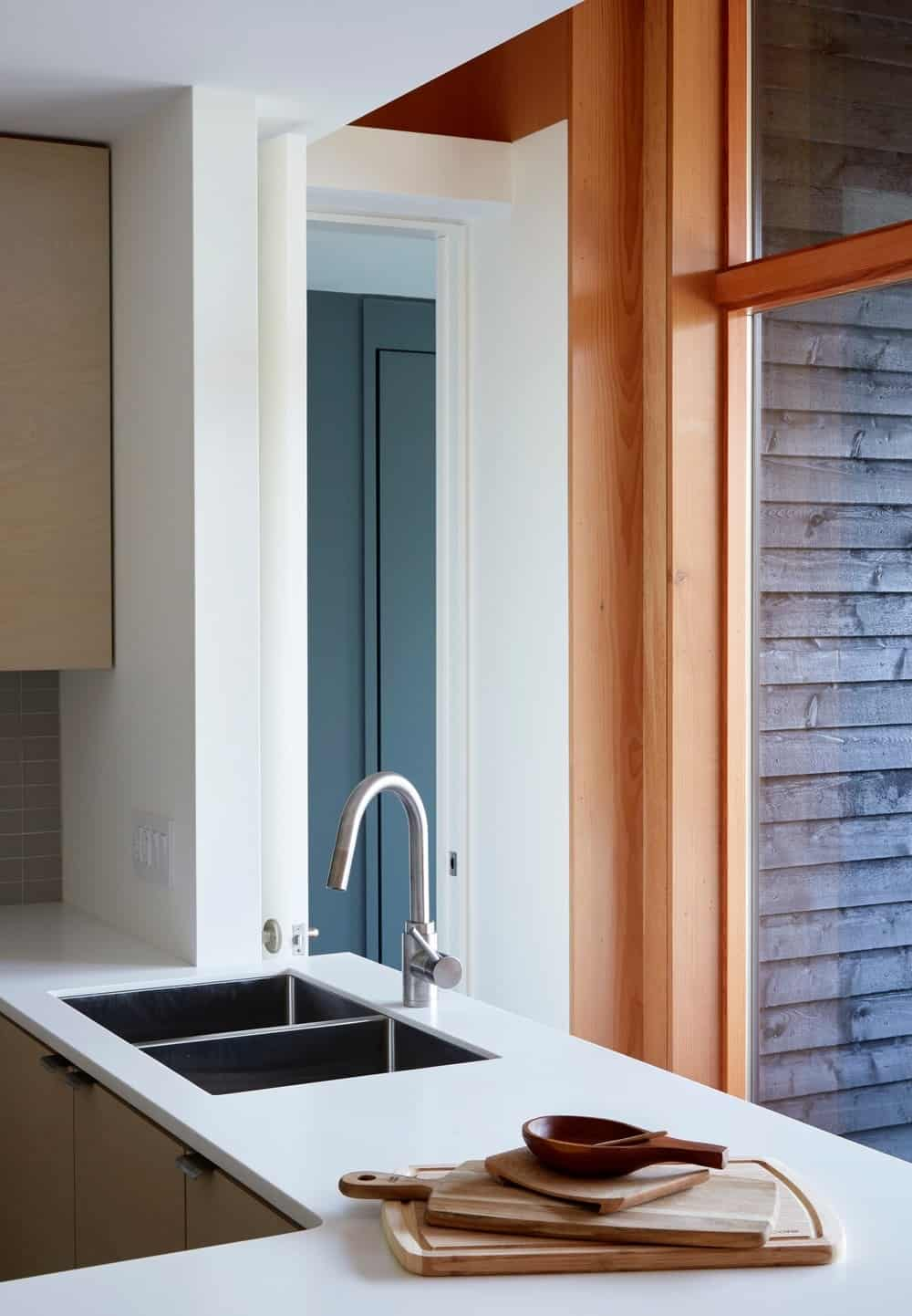 Kitchen featuring white walls and smooth white countertops with a single sink. Photo credit: Janet Kimber