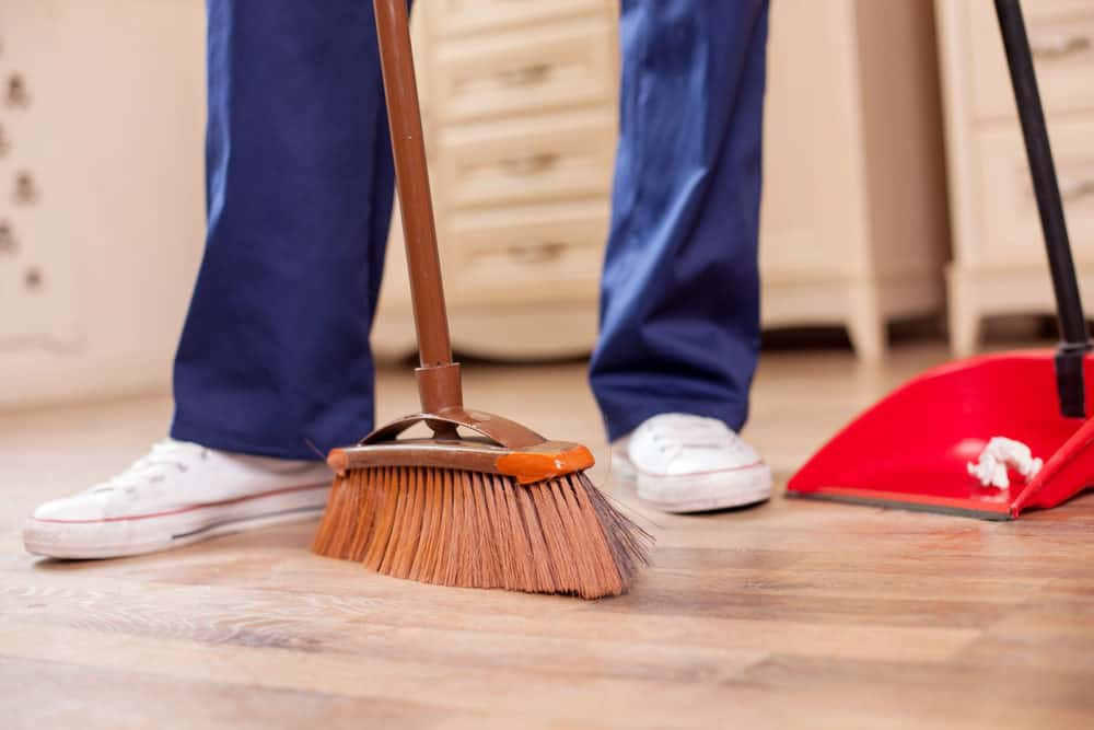Man sweeping the floor with broom and upright dust pan