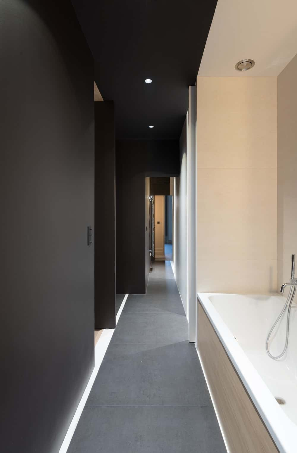 Contemporary bathroom with a corner tub lighted by recessed ceiling lights. Photo credit: Mickaël Martins Afonso